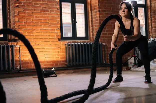 Портрет молодой спортивной женщины фитнеса с сильным красивым телом в черной спортивной одежде, тренирующейся с боевыми веревками, имеющими тренировку. мускулистые кавказские женские тренировки в темном тренажерном зале.