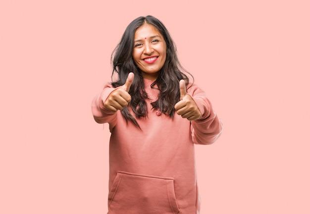 陽気で興奮して、笑みを浮かべて、彼女の親指を上げる、成功と承認、okのジェスチャーの概念フィットネス若いインド人女性の肖像