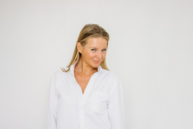 分離した白い壁の背景に白いシャツに長い髪といちゃつく金髪40年女性の肖像画