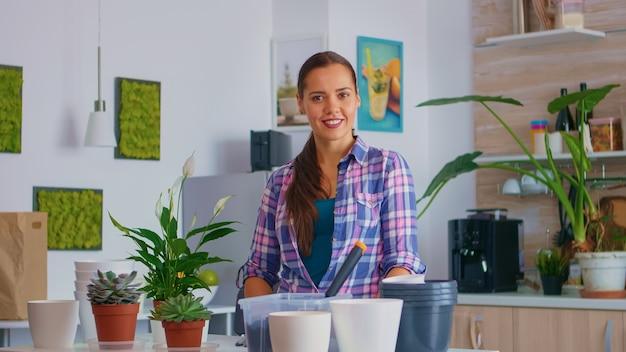 ガーデニング手袋を使用して自宅で働く花屋の女性の肖像画。シャベルで肥沃な土壌をポット、白いセラミック植木鉢、ハウスフラワーに使用し、家の装飾のために植え替えるために準備された植物