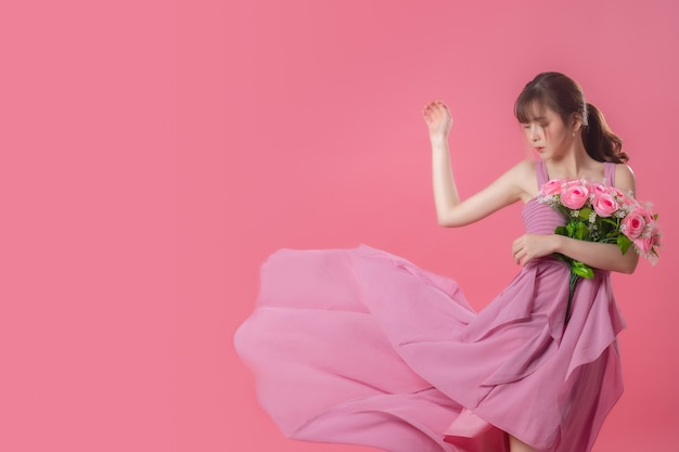 ピンクに花びらが飛んで流れるピンクのドレスの肖像画
