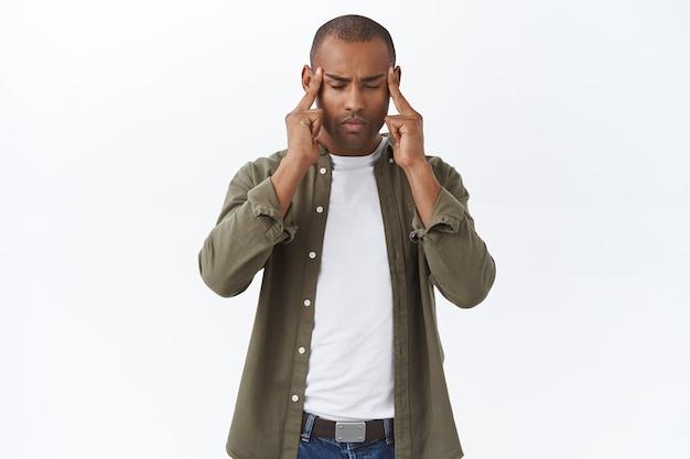 Портрет сосредоточенного, афроамериканского мужчины, который чувствует стресс, пытается успокоиться и набраться терпения, массирует виски, закрывает глаза