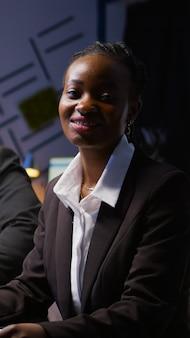 残業ノートブックに投資戦略を書く集中アフリカ系アメリカ人女性の肖像画