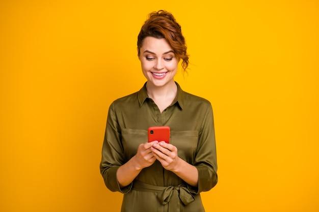 Портрет сосредоточенной веселой девушки, отправляющей текстовые сообщения онлайн-телефону