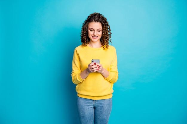 Портрет сосредоточенной жизнерадостной девушки, использующей гаджет устройства, отправляет смс, изолированные на синем фоне