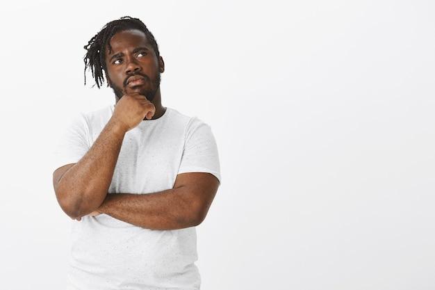 Портрет сосредоточенного парня с косами, позирующего на фоне белой стены