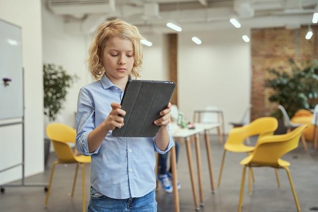 줄기 수업 중에 카메라를 위해 포즈를 취하는 동안 태블릿 pc를 사용하는 집중된 어린 소년의 초상화