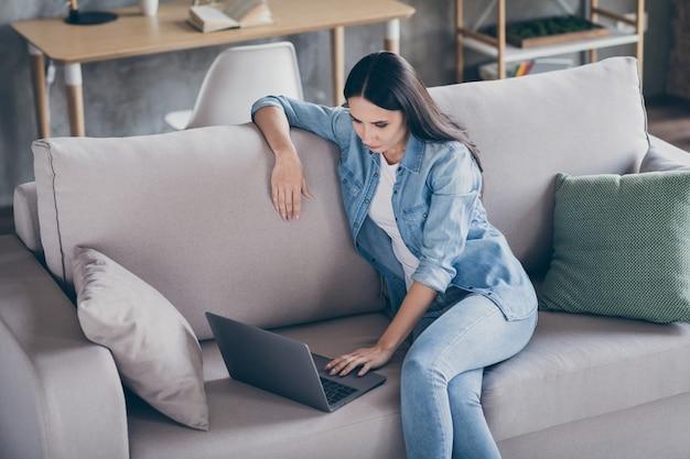 Портрет сосредоточенной девушки-менеджера, работающей в домашнем офисе, используя ноутбук, читать ошейник, генеральный директор, отчет о запуске, смотреть коучинг, онлайн-обучение, учеба, сидеть на диване в доме, в помещении