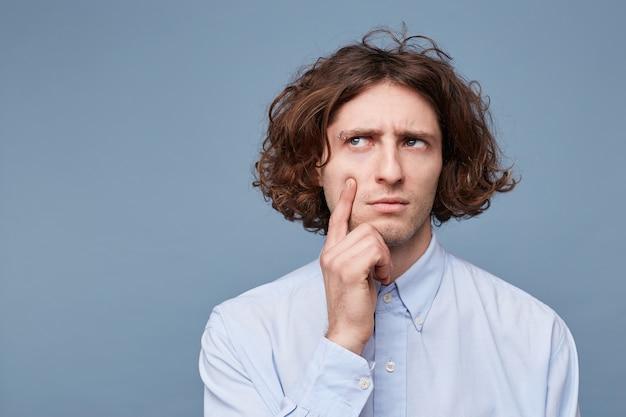 長い乱雑な髪を持つ焦点を絞ったスマートで創造的な男性の肖像画