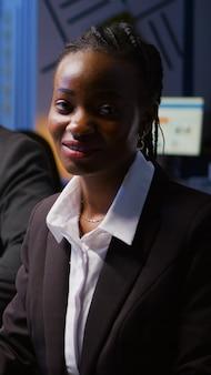 管理のインフォグラフィックで残業している会社のオフィスの会議室の机に座っている焦点を当てた笑顔のアフリカの女性の肖像画。深夜に戦略を分析する多様な多民族チームワーク
