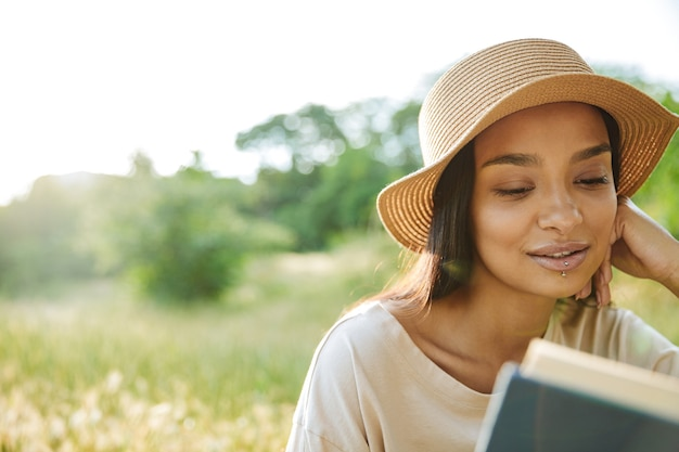 Портрет сосредоточенной женщины с пирсингом в губе и соломенной шляпе, читающей книгу, сидя на траве в зеленом парке