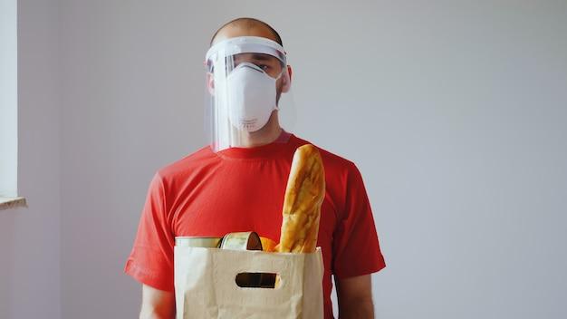 Covid-19の間にマスクを持った食品配達人の肖像画。