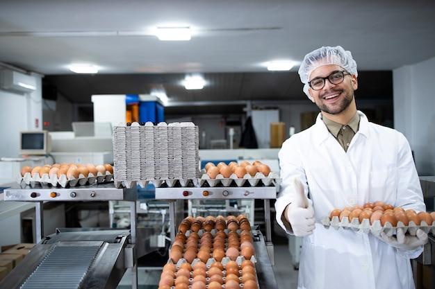 헤어 넷 및 식품 가공 공장에서 산업 운송 및 포장 기계에 의해 계란을 들고 위생 장갑 식품 공장 노동자의 초상화.