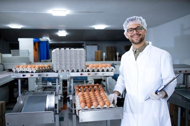 Портрет работника пищевой фабрики с сеткой для волос и гигиенических перчаток, стоящего у машины для промышленной транспортировки и упаковки яиц на пищевом заводе.