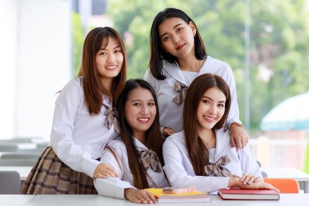 日本、韓国風の女子高生の制服を着て、4つのキュートで若いアジアの女の子のグループの肖像画。
