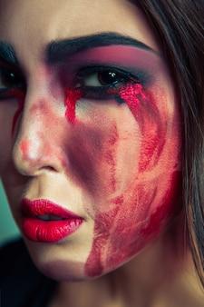 彼女の顔に汚い色の化粧を台無しにしたフリークモンスターの肖像画。赤い血の涙と手で泣いている女性。緑の背景にハロウィーンのコンセプトです。スタジオショット、ダークブラウンの目。