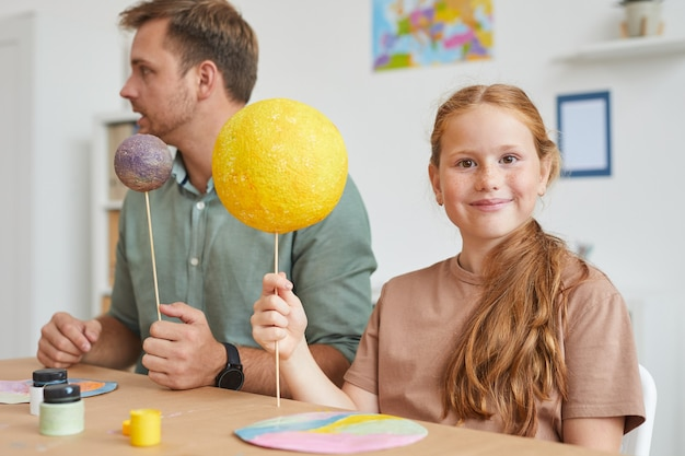 学校や開発センターでアートとクラフトのクラス中に惑星モデルを保持しながら笑っているそばかすの赤い髪の少女の肖像画