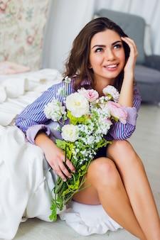 Портрет свежей довольно веселой брюнетки в полосатой футболке, сидящей на полу с весенними цветами в руках