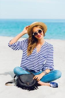 クールなサングラスと太陽が降り注ぐ熱帯のビーチに座っている麦わら帽子の新鮮な若い女性の肖像画