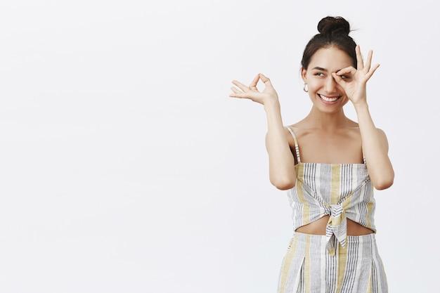 Портрет дружелюбной беззаботной и элегантной женщины с прической в виде пучка в соответствующем наряде, демонстрирующей жест «окей» или «окей», держащей пальцы нулевым знаком над серой стеной