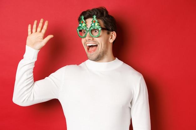 パーティーグラスと白いセーターでフレンドリーで陽気な男の肖像画、こんにちはと言って左を見て、友人に挨拶、赤い背景の上に立って