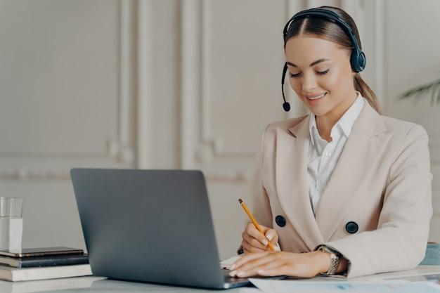 ラップトップコンピューターでのweb会議に参加しているマイク付きヘッドセットを身に着けているフレンドリーな女性ceoの肖像画、職場に座ってメモを書くフォーマルなスーツの前向きな若い実業家