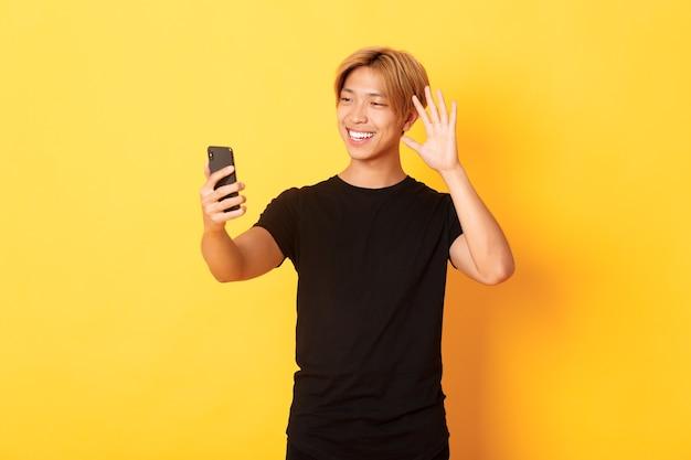 フレンドリーなハンサムなアジア人男性の肖像画、笑顔でスマートフォンに手を振って、ビデオ通話で友達に挨拶、黄色の壁に立って