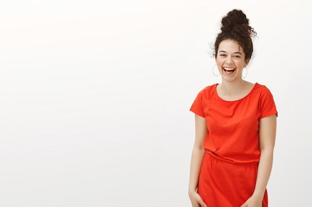 세련된 빨간 드레스에 곱슬 머리를 가진 친절하고 긍정적 인 여자의 초상화, 큰 소리로 웃고 행복에서 웃고