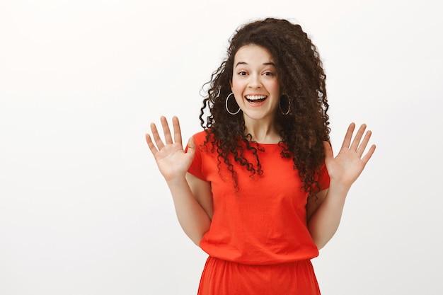 赤いドレスの巻き毛を持つフレンドリーな外観のスタイリッシュなヨーロッパの女性の肖像画、友人との予期しない会議から手のひらを上げる