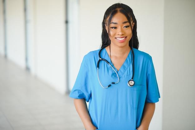 Портрет дружелюбного, улыбающегося уверенно женского медицинского работника с лабораторным гербом, скрещенными руками, держащими очки. изолированная предпосылка клиники больницы.