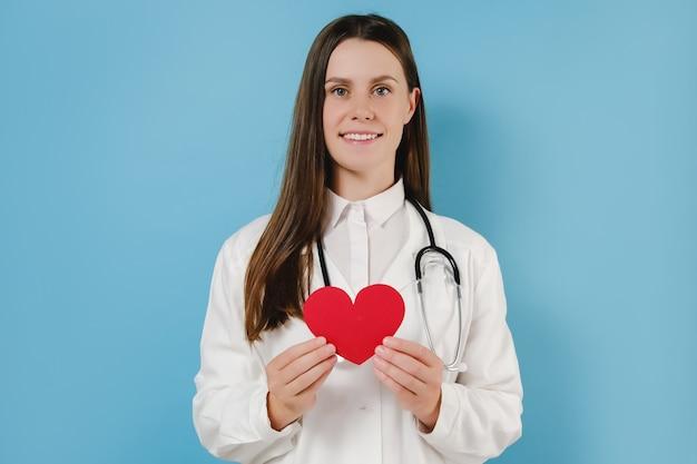 청진기가 작은 붉은 심장을 안고 있는 흰색 전문 의료 유니폼을 입은 친근한 미소를 짓고 있는 젊은 여성 의사의 초상화