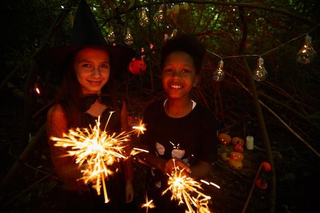 暗い森に立って、一緒にハロウィーンを祝っている間、線香花火を持ってカメラに微笑んでいる友人の肖像画