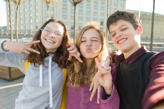 Портрет друзей подростка мальчик и две девочки улыбаются