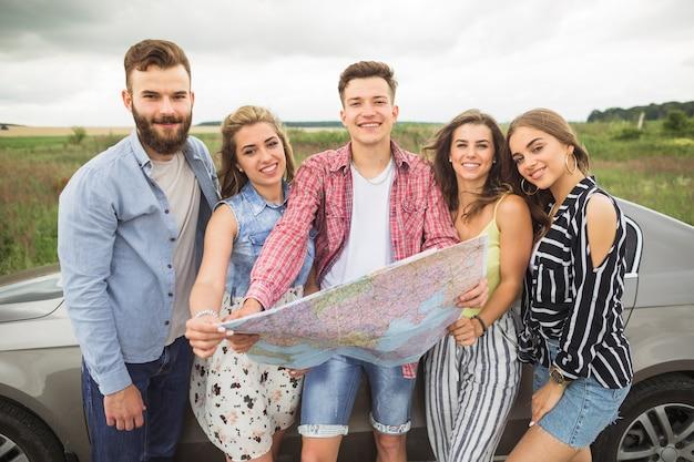 Портрет друзей с туристической картой, стоящей у автомобиля