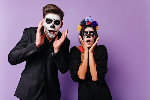 Портрет испуганных и потрясенных мальчика и девочки. пара с фейс-артом в день всех мертвых в темных нарядах позирует на сиреневой стене.