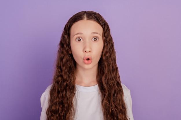 紫色の背景に分離されたおびえた子供の肖像画