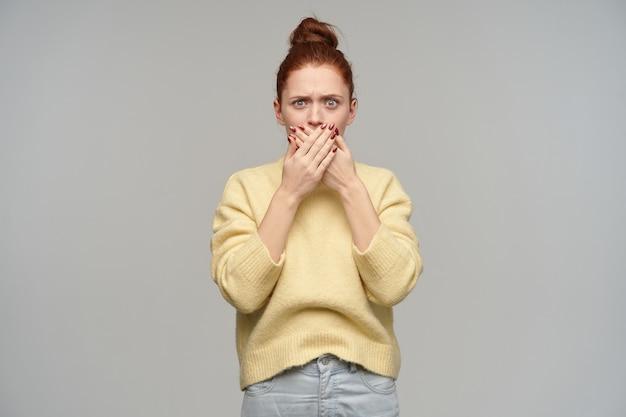 머리를 찡그림, 성인 빨간 머리 여자의 초상화는 롤빵에 모여. 파스텔 옐로우 스웨터와 청바지를 입고. 손바닥으로 입을 가리십시오. 회색 벽 위에 절연