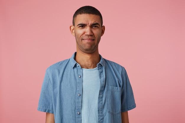 ピンクの背景の上に立っている、しわがれた唇で眉をひそめているうんざりした暗い肌の少年の肖像画は、反発的で不快なものを見ました。人と感情の概念。