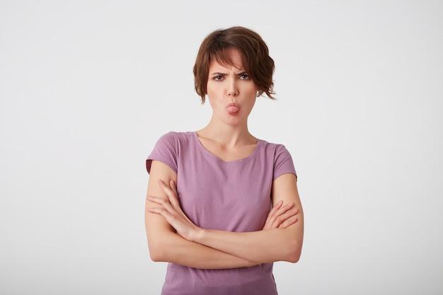 空白のtシャツを着た眉をひそめている不機嫌な短髪の女性の肖像画は、腕を組んで決定を疑って、白い壁の上に舌が立っていることを示しています。
