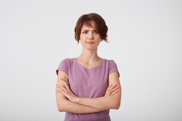 空白のtシャツを着た眉をひそめている不機嫌な短髪の女性の肖像画は、腕を組んで決定を疑って、白い壁の上に立っています。