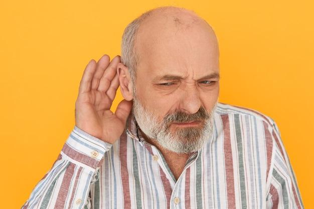 Портрет хмурого разочарованного бородатого пенсионера в полосатой рубашке, держащего руку у уха, внимательно слушающего, пытающегося расслышать невнятный разговор. проблемы со слухом и подслушивание