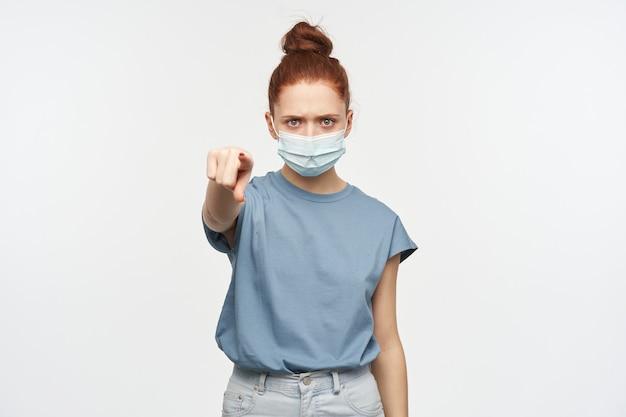 머리를 찡그림, 심각한 빨간 머리 소녀의 초상화는 롤빵에 모여. 파란색 티셔츠, 청바지 및 안면 보호 마스크를 착용하십시오. 당신을 가리키고 있습니다. 흰 벽 위에 절연