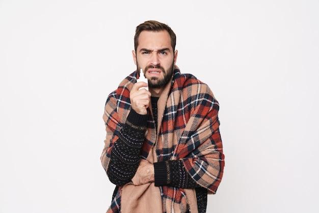 Портрет замороженного кавказского парня, завернутого в одеяло, с каплями в нос из-за гриппа, изолированного над белой стеной