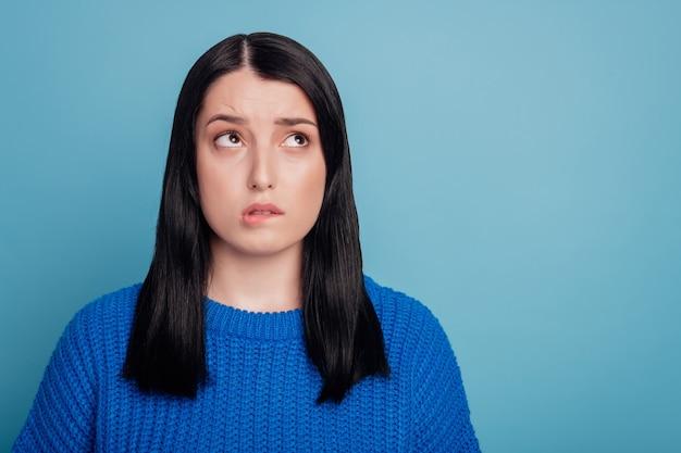 欲求不満の恐怖の女の子の肖像画コピースペース噛む唇の歯は紫色の背景の上に分離されたスタイリッシュな流行のセーターを着る