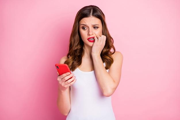 Портрет разочарованной девушки кусает ногти мобильным телефоном