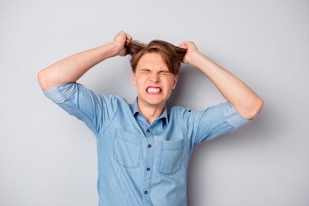 Портрет расстроенного возмущенного злого парня, у которого много рутины работы, терять самообладание, чувствовать себя измученным, держать его стрижку, закрыть глаза, носить стильную одежду, изолированную над серой стеной