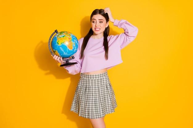 欲求不満の女子高生の肖像画は地理のレッスンを保持します地球