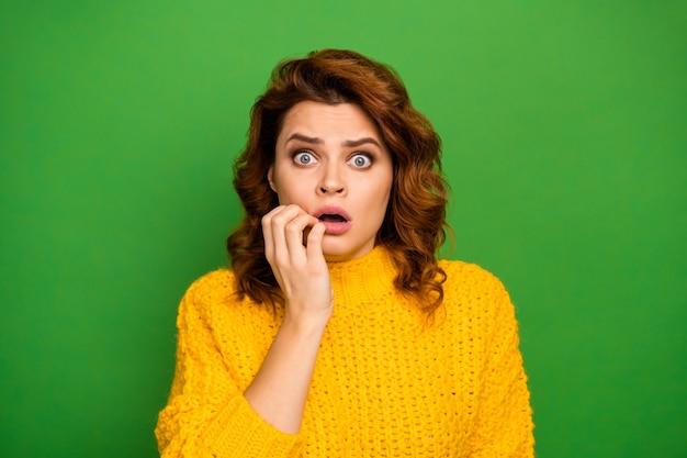 欲求不満の動揺した神経質な女性の肖像は恐ろしい仕事の間違いのニュースを聞く絶望を感じる指を噛む爪は鮮やかな色の壁の上に隔離されたニットの暖かいジャンパーを着る