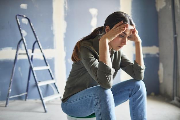 Портрет разочарованной молодой женщины, сидящей на банке с краской, опустошенной проектом ремонта, копия пространства