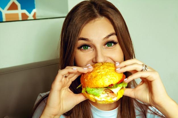 녹색 눈을 가진 재미 갈색 머리 여자의 초상화는 햄버거를 먹는